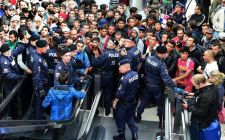 AUS01SALZBURGO (AUSTRIA) 15/09/2015.- Policías forman un cordón frente a los cientos de refugiados que esperan la llegada de más trenes con dirección a Alemania en la estación de Salzburgo (Austria), hoy, 15 de septiembre de 2015. EFE/Barbara Gindl